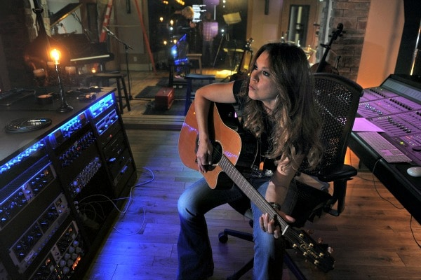 Grechen Wilson plays guitar in her studio before a session with her band. Photo: artisthomeandstudio.com